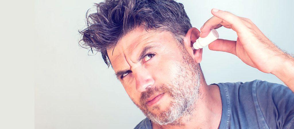 Man applying earwax softener drops into his ear