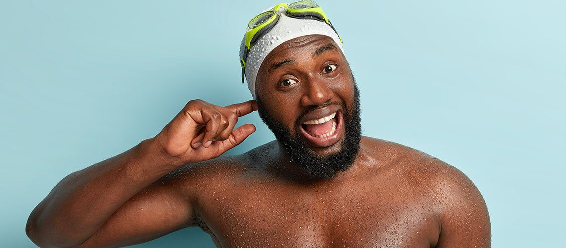 Happy African man has water in his ear after swimming